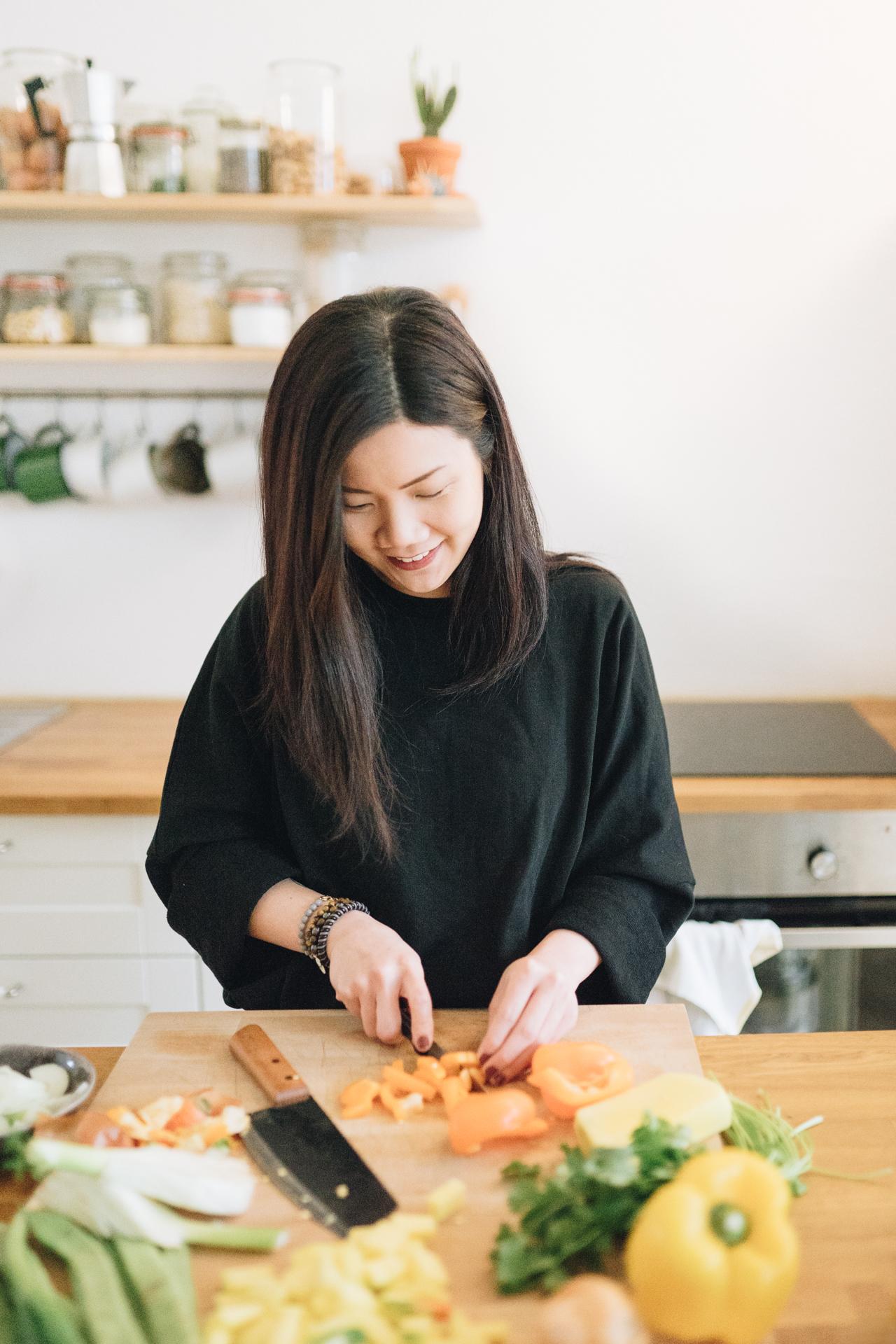 Frau schneidet Paprika in der Küche