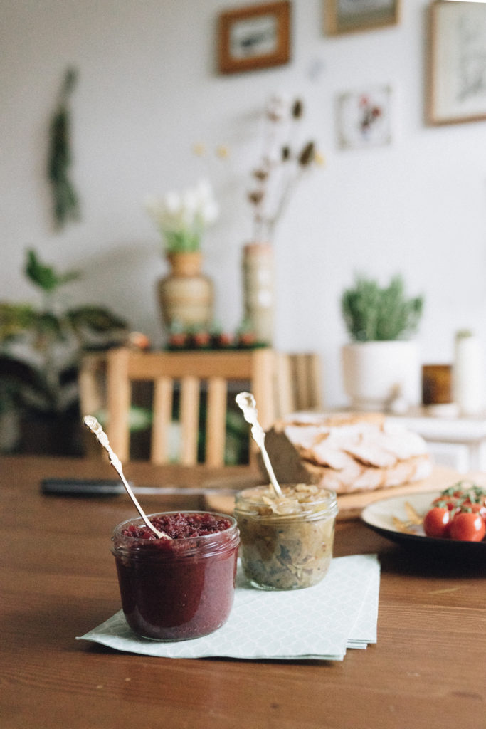 Holztisch gedeckt mit Chutneys, Brot und Tomate