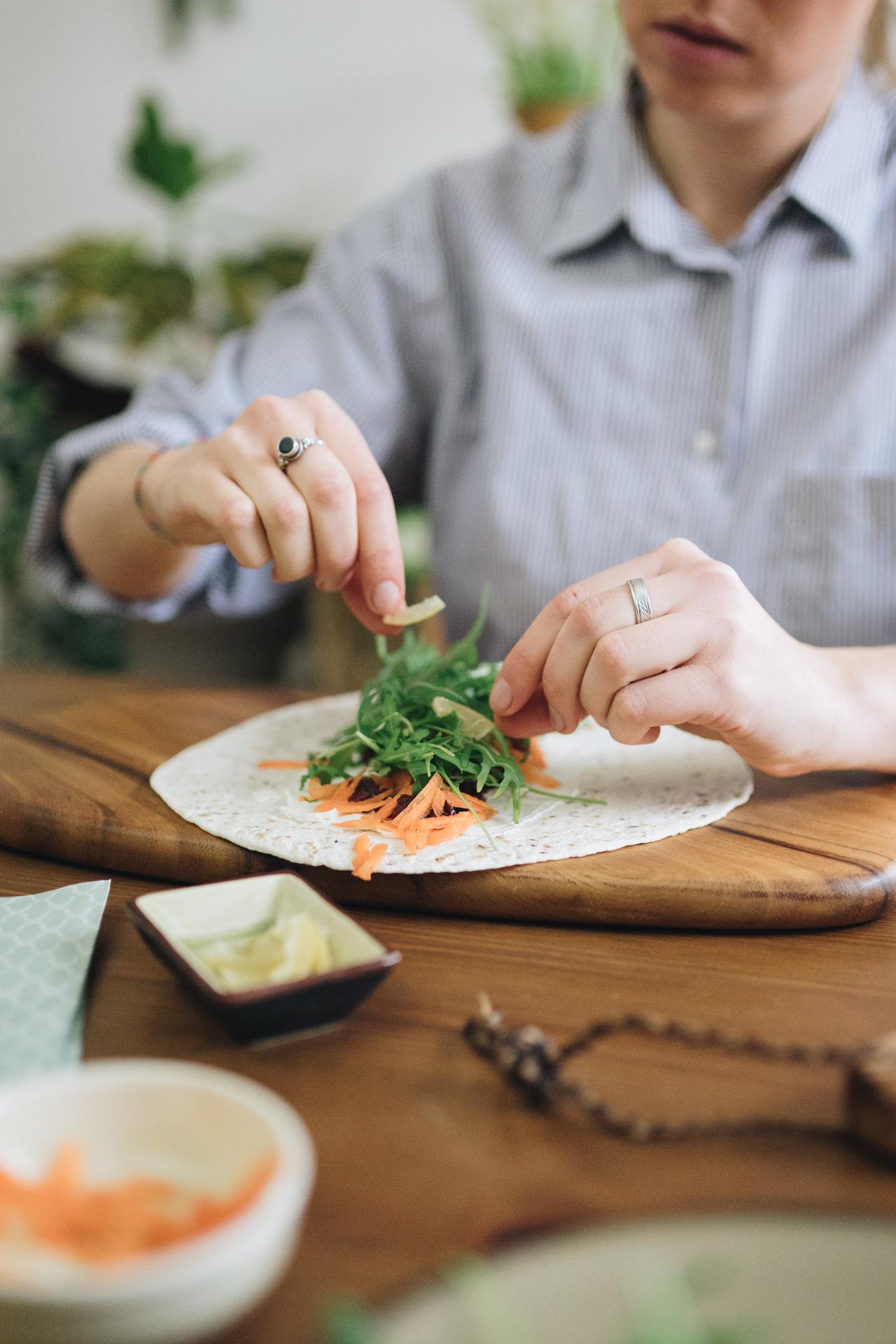 Frau füllt Tortilla Wrap mit Gemüse