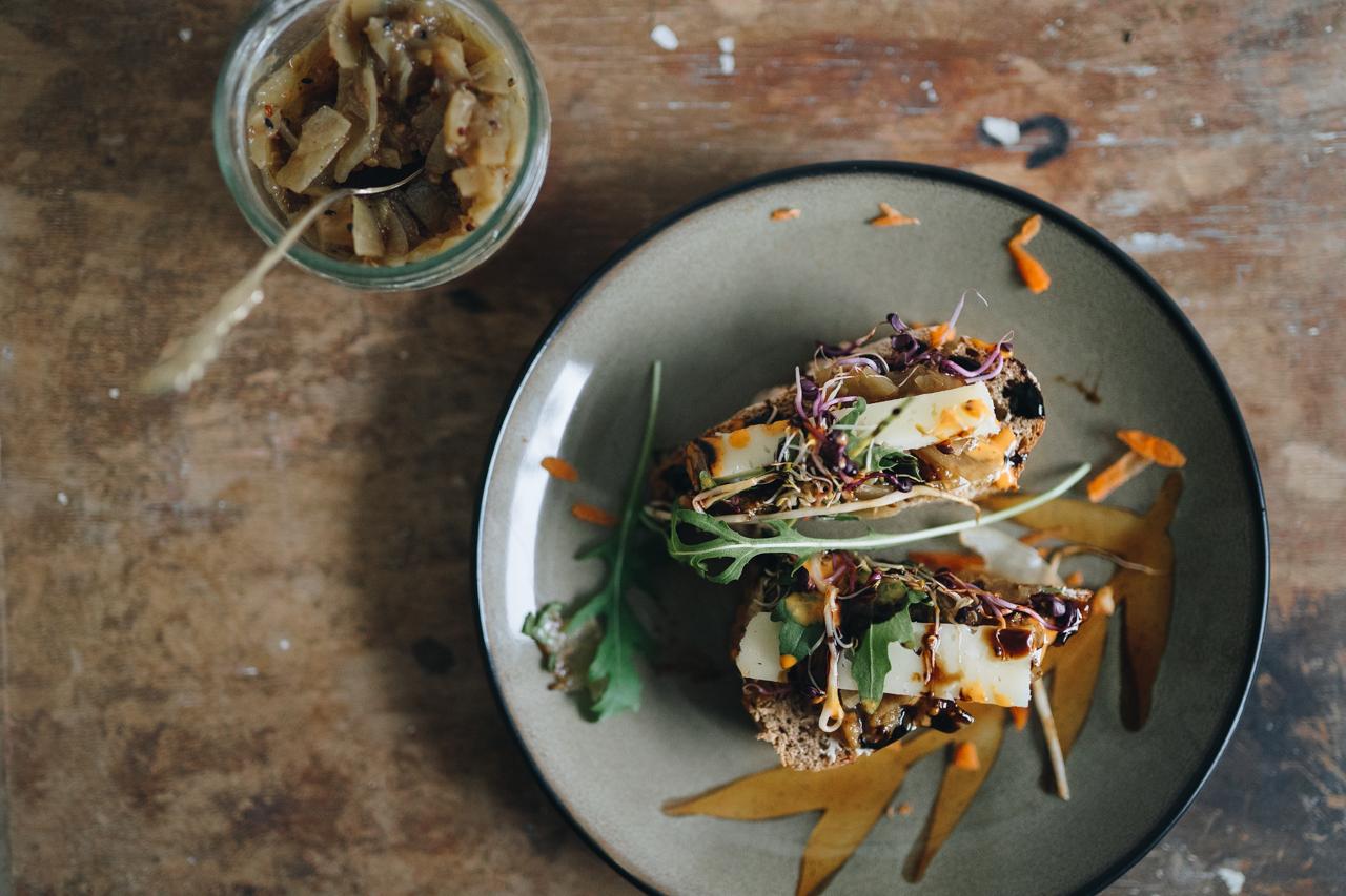Ein Teller mit Brot belegt mit Käse, Gemüse und Chutney
