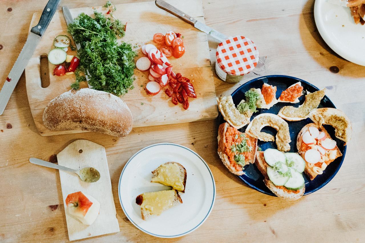 Einen Teller mit verschiedene belegte Brote auf einem Holztisch