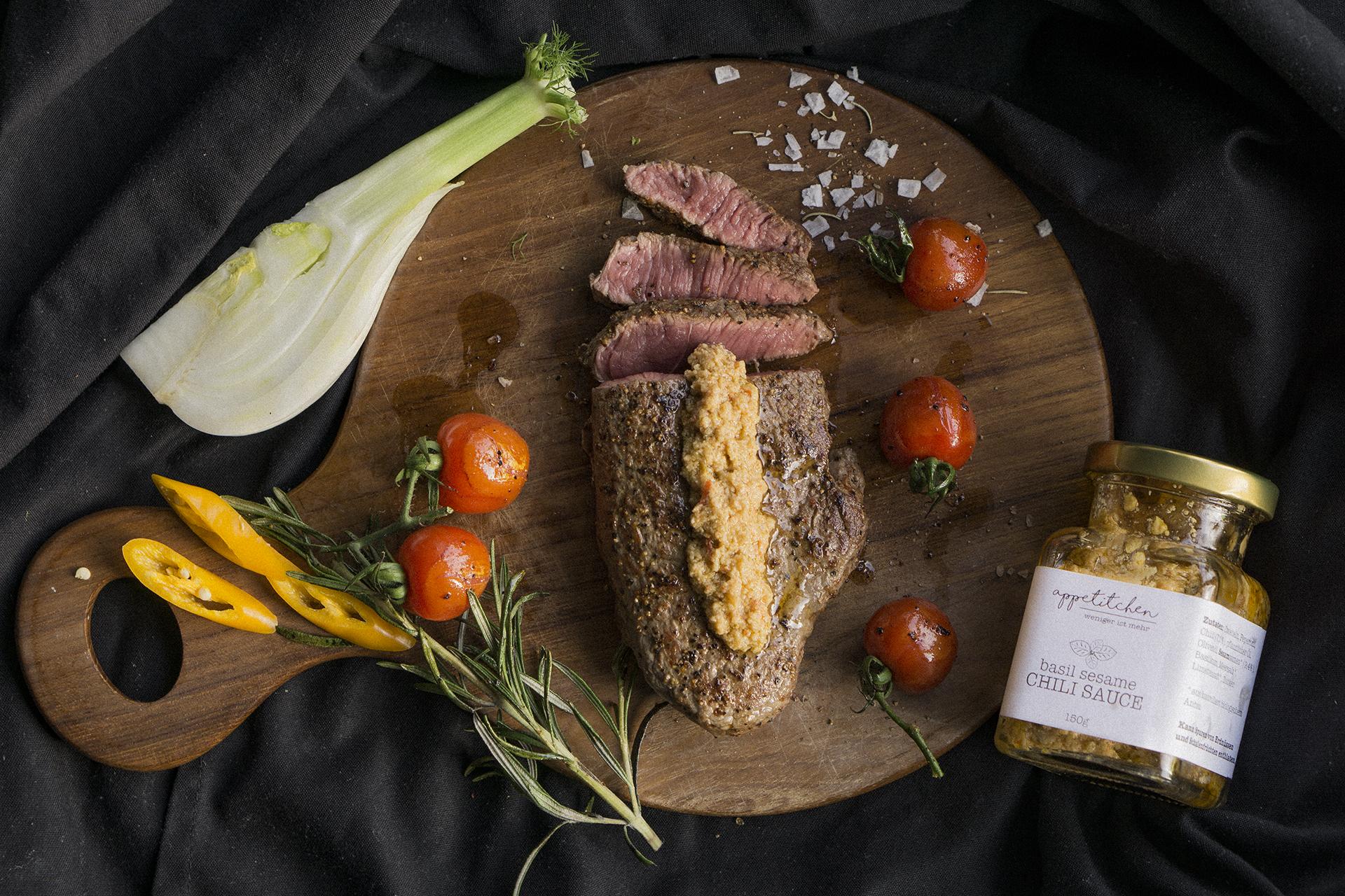 Medium Rare Steak auf einem Brett mit Gemüse und Chili Sauce
