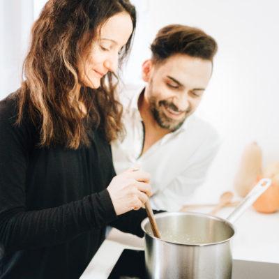 Mann und Frau beim Kochen am Herd