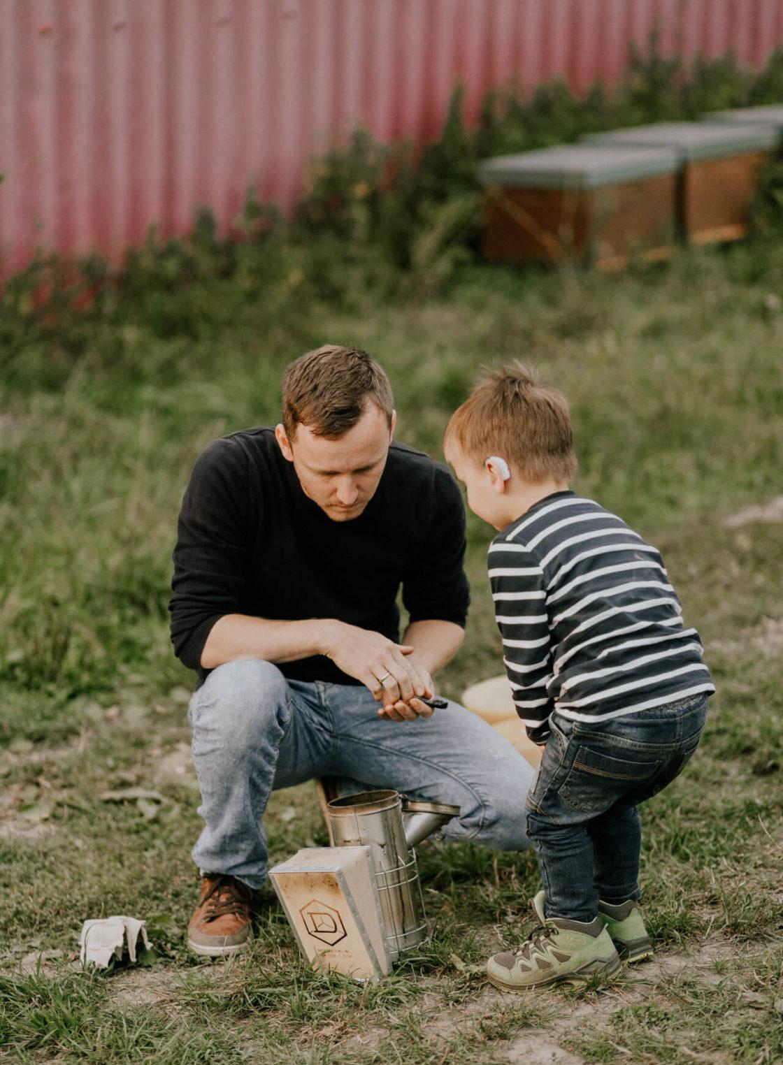 Mann und Kind beim imkern Grega's Imkerei