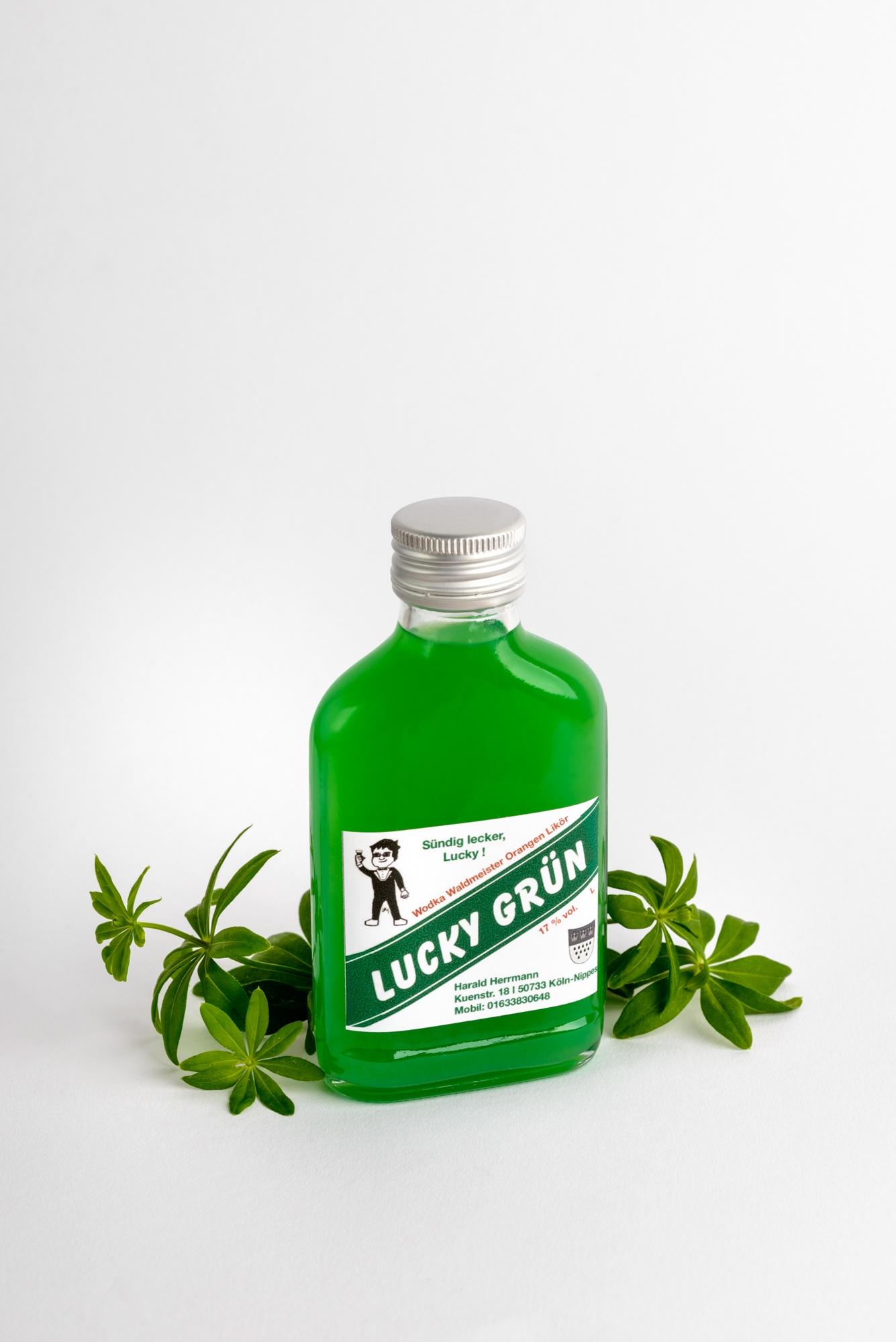 Eine kleine Flasche Wodka Waldmeisterlikör mit Waldmeisterpflanze