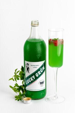 Eine große Flasche Wodka Waldmeisterlikör mit Waldmeisterpflanze und Sektglas