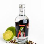 Eine Flasche Gin mit Limette und Pfeffer