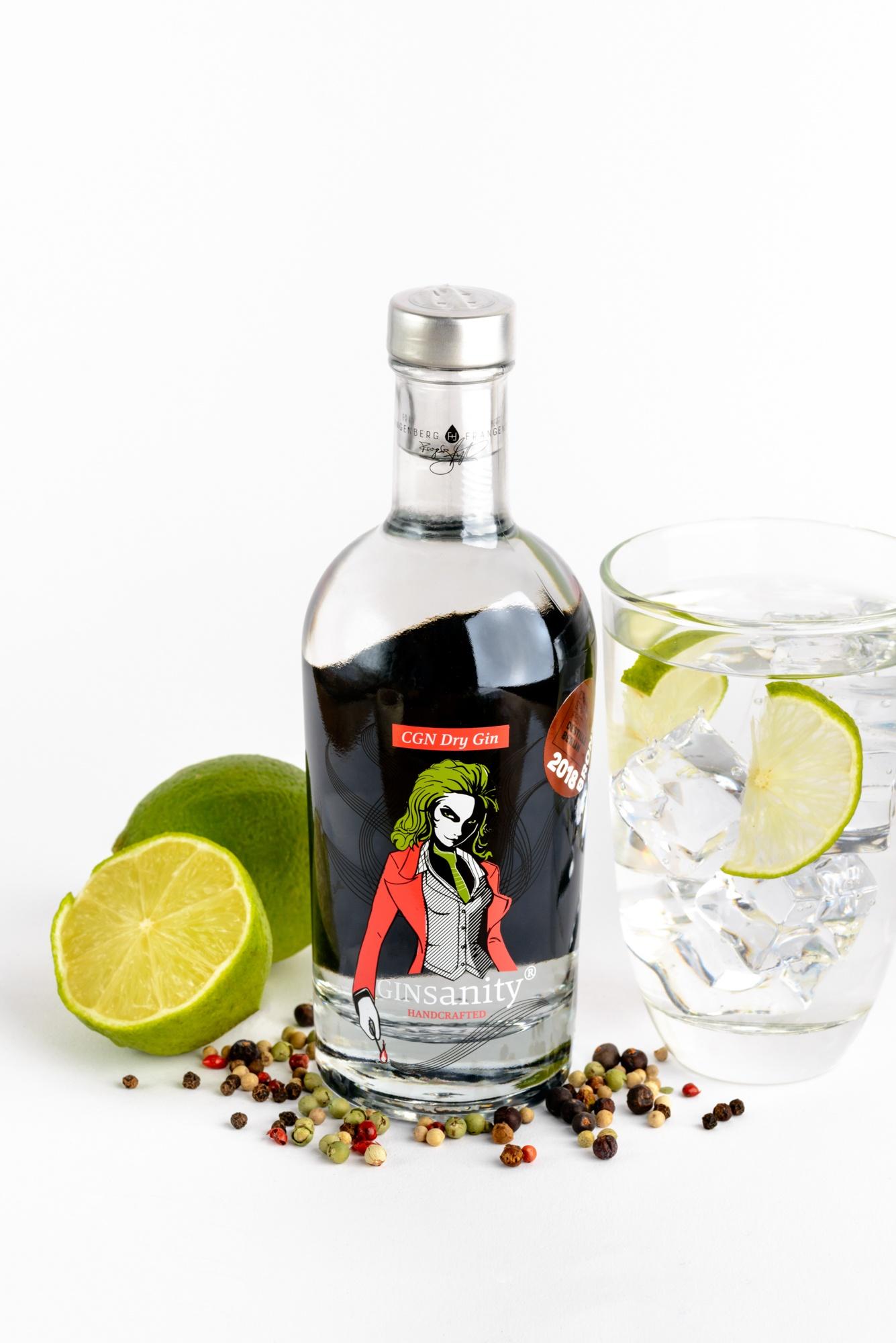 Eine Flasche Gin mit Gin Tonic, Limette und Pfeffer