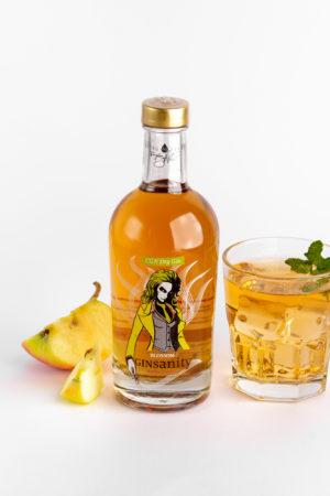 Eine Flasche orangfarbener Gin mit Cocktail mit Äpfel und Minze