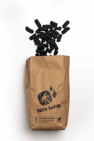 Eine offene Packung Grillkohle Briketts aus fairem Handel