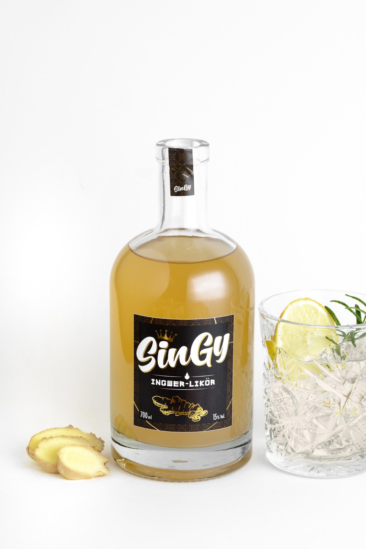 Eine Flasche Ingwerlikör mit einem Glas Ingwerlikör-Tonic